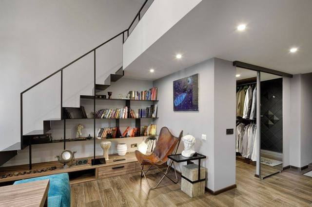 Gầm cầu thang dẫn lên gác được tận dụng tối đa làm giá sách và nơi trưng bày những đồ lưu niệm. Ngay kế bên là một phòng nhỏ vừa có tác dụng là phòng thay đồ vừa là nơi để những đồ dùng không cần thiết. Phía đối diện là khu vực vệ sinh.
