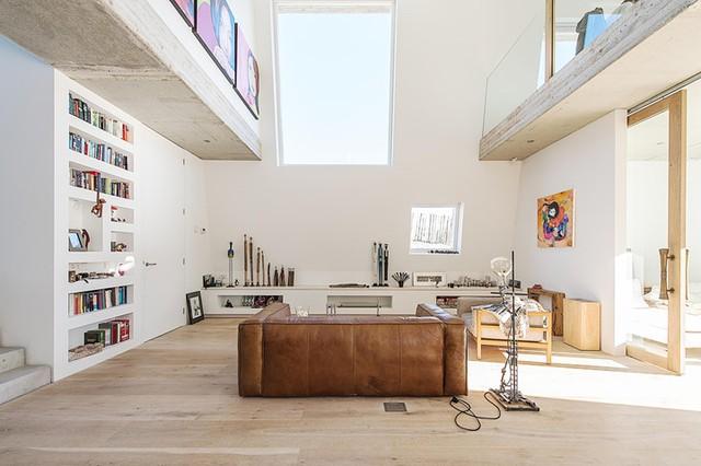 Không gian phòng khách tràn ngập ánh sáng tự nhiên và được bài trí khá đơn giản với ghế sofa, bàn trà cùng kệ để đồ vô cùng xinh xắn.