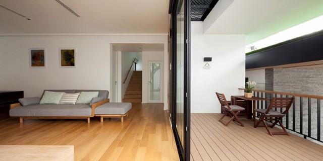 Ngay phía bên trong là phòng khách được bài trí đơn giản với bộ ghế sofa có chân tạo sự thông thoáng và thanh thoát cho ngôi nhà.