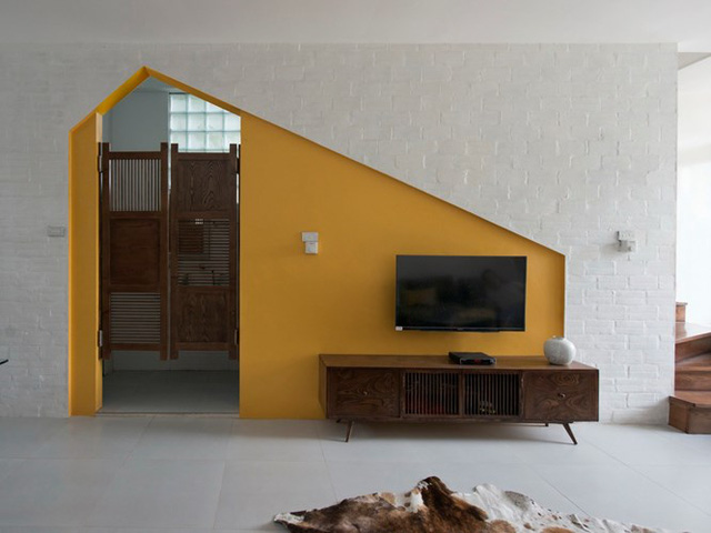 Bức tường màu vàng nơi phòng khách là điểm khác biệt nhất của căn nhà.