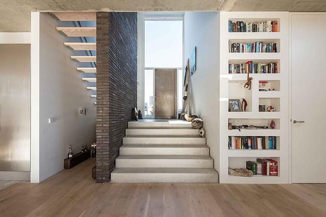 Một cầu thang nhỏ uốn lượn quanh bức tường gạch xám màu là lối dẫ lên trên các tầng của ngôi nhà.