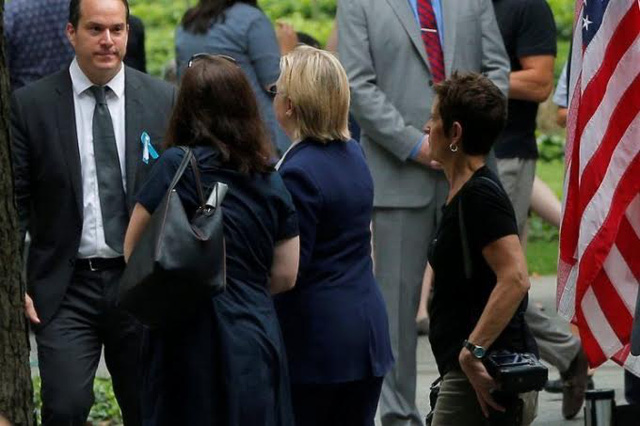 Bà Clinton được trợ lí dìu đi sau khi bị choáng vì mất nước do nóng tại buổi lễ tưởng niệm nạn nhân 11/9. Ảnh: Reuters.