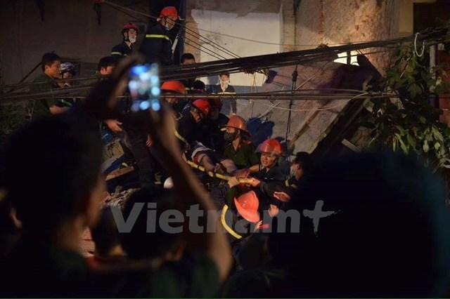 Mái nhà đè lên phần kiến trúc ở dưới, lực lượng cứu hộ tiếp cận các nạn nhân bị mắc kẹt rất khó khăn. (Ảnh: Minh Sơn/Vietnam+)