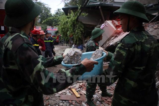 Đội cứu hộ xếp hàng vận chuyển đất đá ra ngoài bằng tay và xô chậu. (Ảnh: Minh Sơn/Vietnam+)