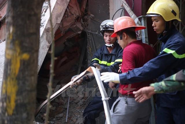 Để đưa được một thanh sắt ra ngoài lúc này, đội cứu hộ cũng phải rất vất vả. (Ảnh: Minh Sơn/Vietnam+)