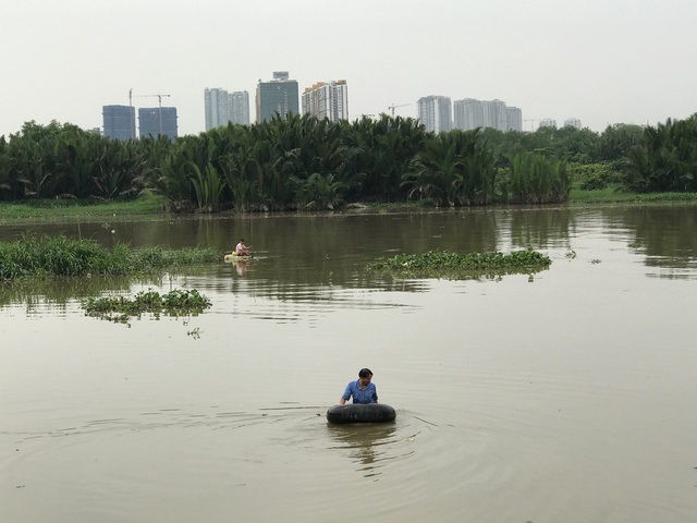 Người dân nghèo khó vẫn hàng ngày mưu sinh trên con sông chảy ngang khu dân cư.