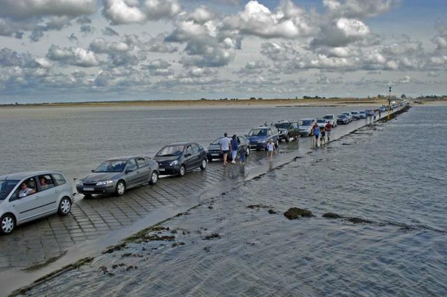 """Các tấm pa-nô đặc biệt được treo dọc theo hai bên đường để cảnh báo cho người đi đường về tình trạng ngập nước ở đây. Và điều hiển nhiên, tình trạng tắc đường đôi khi vẫn xảy ra tại con đường này, đây giống như một """"thử thách"""" nguy hiểm đặc biệt vào khung giờ thủy triều đang dâng."""