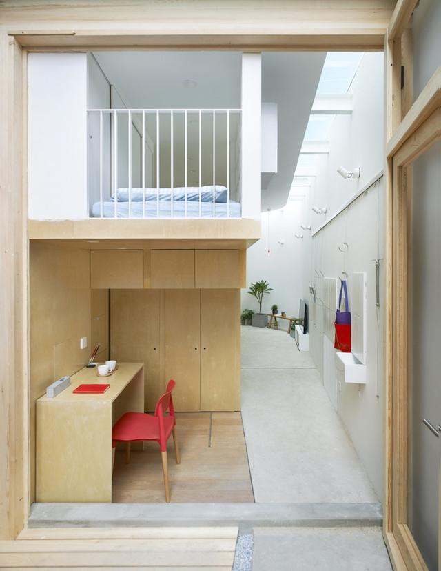 Ngôi nhà sử dụng một hệ kệ gỗ lớn với toàn bộ không gian chức năng được bố trí theo hình chữ L.