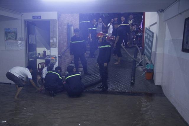 Lực lượng PCCC đang hút nước để cứu một số xe máy tại một chung cư trên đường Phan Xích Long (quận Phú Nhuận, TP HCM)