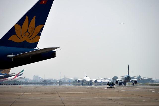 Hình ảnh máy bay nối đuôi nhau trên đường lăn ra vị trí cất cánh như thế này thường xuyên diễn ra ở Cảng hàng không quốc tế Nội Bài (Hà Nội). Tàu của các hãng hàng không lần lượt lăn ra đường băng, phía trên một chiếc máy bay đang chuẩn bị hạ cánh.