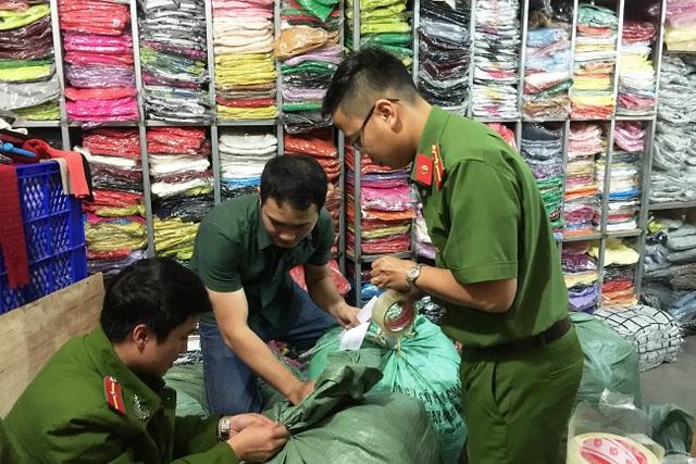 Lực lượng Công an đang thu giữ sản phẩm áo len không rõ nguồn gốc tại cửa hàng của bà Nguyễn Thị Ngọc Hải