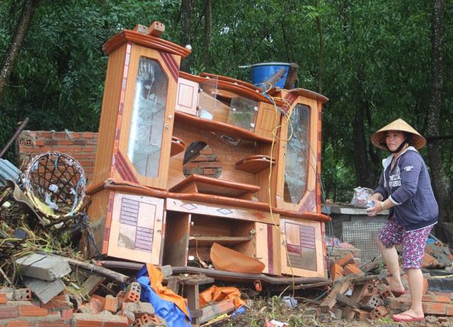 Chị Tô Thị Minh Thủy thu gom một số đồ dùng còn sót lại sau trận lũ quét ngày 13/12 - Ảnh: THIÊN LÝ/Báo Phú Yên