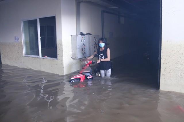 Nước tràn vào hầm ngập cả các tủ điện, nước đã được hút ra ngoài nhưng vẫn còn cao đến đầu gối - Ảnh: NGỌC HIỂN
