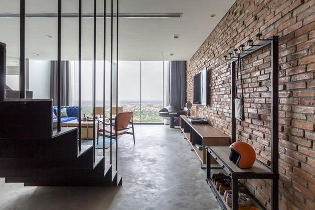 Điểm nhấn đặc biệt của căn hộ này đó là một bức tường gạch thô lớn kết hợp với nền nhà láng xi măng nhẵn bóng tạo không gian vừa lạ mắt nhưng lại vô cùng thân thiện và gần gũi.