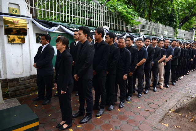 Từ sáng sớm, hàng trăm người mặc đồ đen xếp hàng trước cổng Đại sứ quán Thái Lan (26 Phan Bội Châu, Hà Nội) để chờ viếng nhà vua.