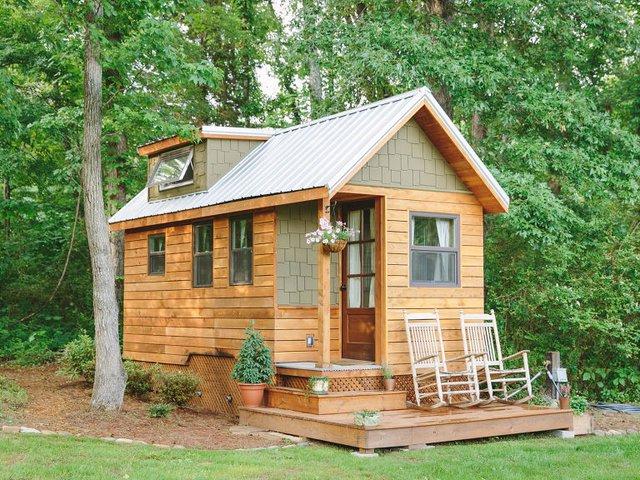 Ngôi nhà gỗ xinh xắn với khoảng sân nhỏ trước hiên nhà nằm yên bình giữa rừng cây xanh mát.