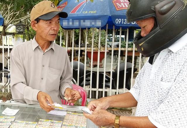 Ông Trần Hưng ở TP Trà Vinh (trái) tỏ ra dè dặt khi bán vé số điện toán in sẵn, vì địa phương này chưa được gắn thiết bị đầu cuối. Ảnh: Việt Tường.