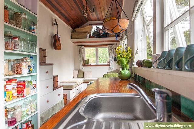 Phía đối diện với bồn rửa là những dãy tủ kệ để những thực phẩm khô. Kệ cửa sổ cũng được tận dụng làm nơi úp cốc chén sau khi rửa.