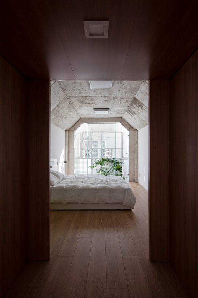 Phòng ngủ với trần bê tông vát cạnh như một căn hầm bí ẩn. Tấm kính dày trong suốt có tác dụng ngăn gió, mưa mỗi khi thời tiết thay đổi.
