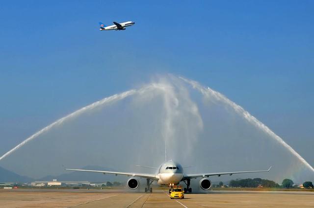 Phía dưới phun vòi rồng chào đón các máy bay mới, trên không máy bay khác vẫn cất cánh bình thường.