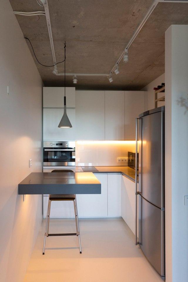 Khu bếp nhỏ được bố trí ở một góc riêng biệt với hệ kệ gỗ. Góc bếp được bố trí gọn, sạch. Chiếc bàn ăn không chân giúp tiết kiệm tối đa diện tích cho gian bếp.