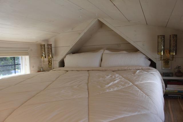 Góc nghỉ ngơi tuy nhỏ nhưng luôn tràn ngập ánh sáng tự nhiên nhờ những ô cửa sổ bằng kính ở hai bên giường ngủ.