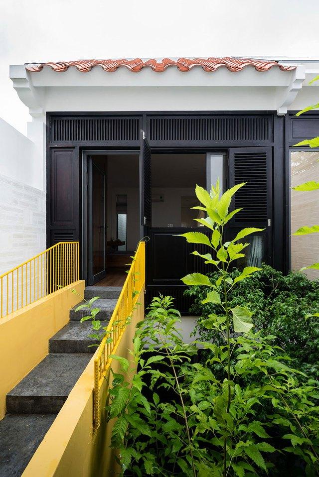 Một cây cầu nhỏ được làm bằng thép màu vàng để kết nối phòng thờ với phần vườn nghiêng bên ngoài.