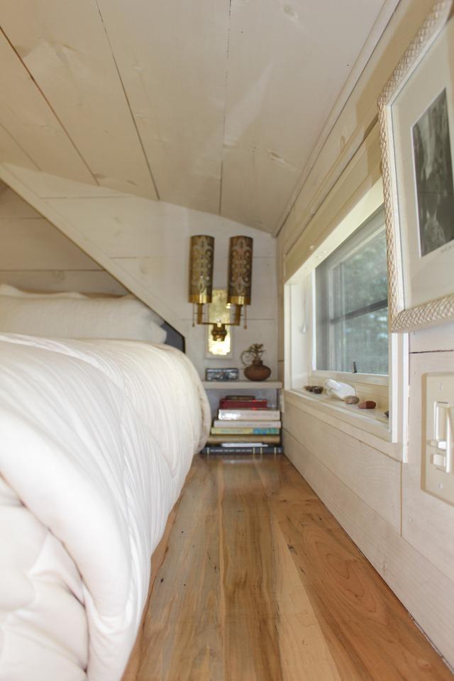 Góc nhỏ nơi đâu giường được gia chủ treo đèn ngủ và một giá sách nhỏ.