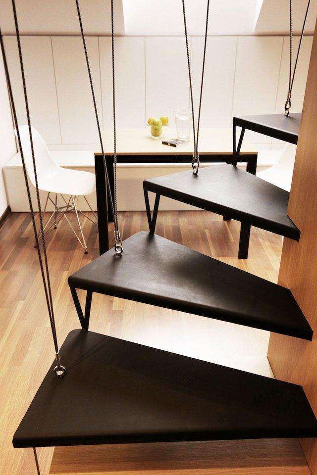 Thay vì làm lan can, chiếc cầu thang dẫn lên gác xép với một đầu được lắp hệ thống cáp treo gắn cố định lên trần nhà. Đầu bên kia gắn chặt vào trụ gỗ.