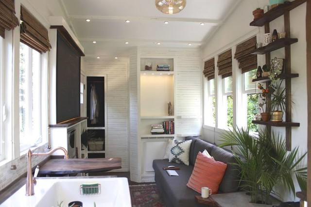 Bên trong ngôi nhà là không gian thoáng sáng với rất nhiều cửa sổ bằng kính. Dù diện tích nhỏ nhưng khu vực tiếp khách được gia chủ chú trọng khi bố trí ghế sofa dài êm ái cùng với những chiếc gối ôm màu sắc dọc cửa sổ.