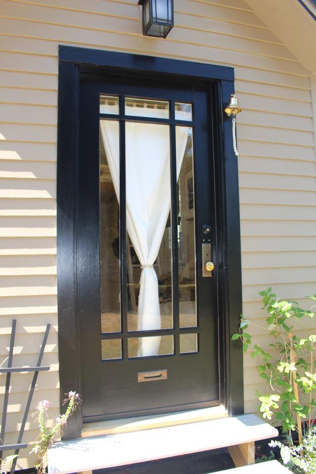 Lối vào được chủ nhà chăm chút với những chậu hoa nhỏ đầy màu sắc trước thềm. Bên trong cửa chính là tấm rèm trắng tạo nét duyên dáng cho ngôi nhà.