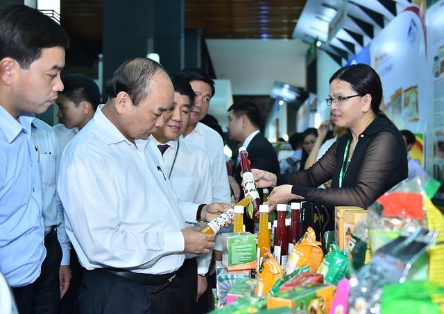 Thủ tướng Nguyễn Xuân Phúc thăm các gian hàng trưng bày sản phẩm nông nghiệp áp dụng công nghệ cao. Ảnh: VGP/Quang Hiếu