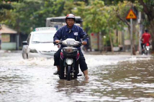 Xe của một người bị giao hàng bị chết máy tại đoạn ngập trên đường Quốc Hương (Q.2) - Ảnh: LÊ PHAN