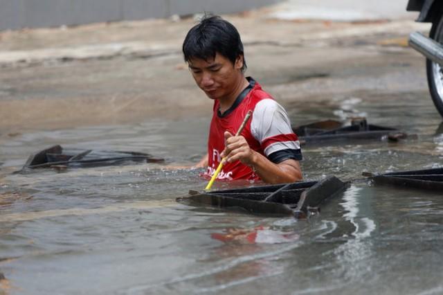 Một nhân viên công ty truyền cáp leo xuống cống ngầm để lắp đặt đường cáp trong khi nước ngập sâu tới phần ngực - Ảnh: LÊ PHAN