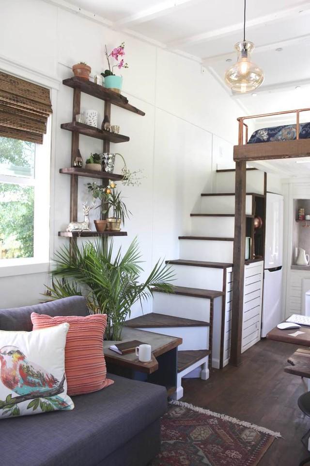 Chiếc bàn trà bằng gỗ xinh xắn cùng với chậu cây xanh được bố trí khéo léo mang đến không gian xanh mát cho ngôi nhà. Bên trên còn được nhấn nhá bằng kệ gỗ với những đồ vật trang trí bắt mắt.