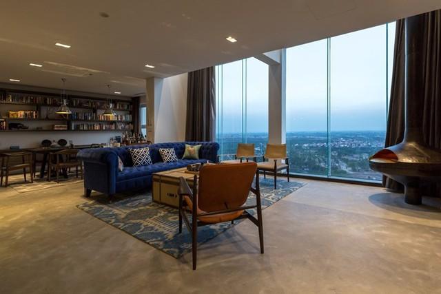 Hệ thống cửa kính cao sát trần nơi phòng khách khiến tầm nhìn được rộng mở và ánh sáng có thể len lỏi vào từng ngõ ngách của căn hộ.