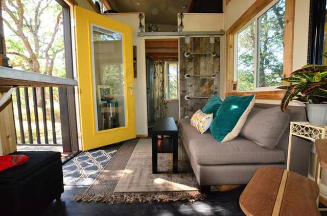Phòng khách với ghế sofa dài êm ái cùng chiếc bàn trà nhỏ xinh được đặt ngay trước lối vào.