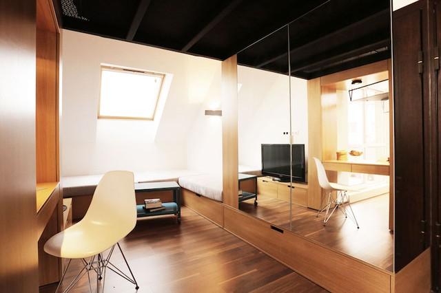 Ngay bên cạnh là phòng khách rộng thoáng, tràn ngập ánh sáng nhờ cửa sổ kính phía trên. Chiếc sofa hình chữ nhật đặt vừa khít góc tường vừa tận dụng tối đa diện tích vừa là một khu trữ đồ với những ngăn kéo bên dưới.