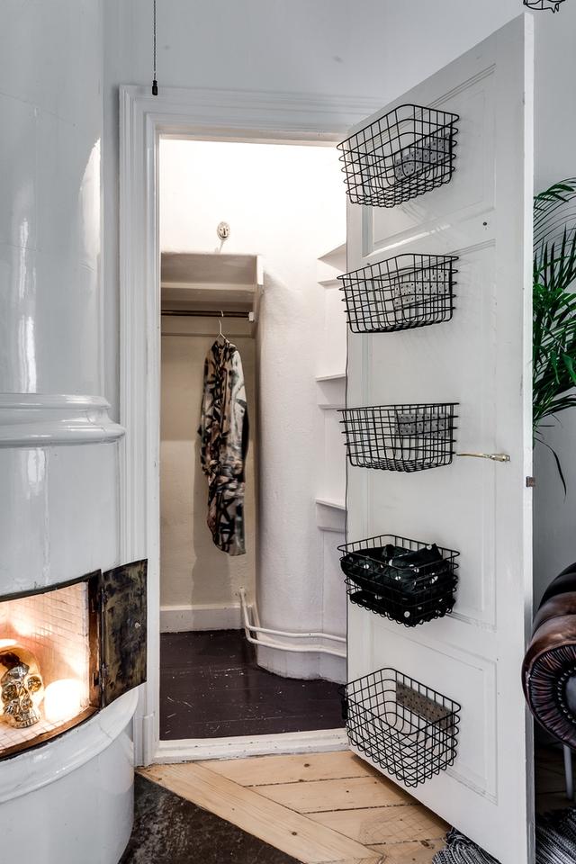 Góc nhỏ nhắn méo mó cạnh lò sưởi phía sau cánh cửa trắng được tận dụng làm tủ để quần áo. Chủ nhà còn vô cùng thông minh khi tạo ra cả một hệ thống giá treo giúp dễ dàng lấy và cất đồ mỗi khi dùng.