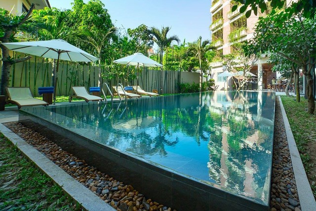"""Bên trong khách sạn còn có một hồ bơi xanh ngắt bao quanh là những bức """"tường cây"""" dựng đứng vô cùng đẹp mắt."""