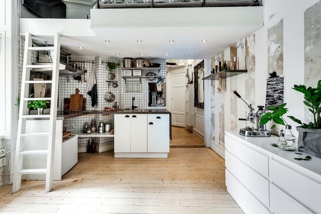 Gian bếp nhỏ xinh được đặt ngay dưới gác lửng. Không dùng hệ thống tủ bếp như những gian bếp thông thường chủ ngôi nhà này đã chọn kệ mở kết hợp với hệ thống móc treo vừa giúp thỏa mãn nhu cầu trữ đồ cho chủ nhà vừa tiện cho người nội trợ.