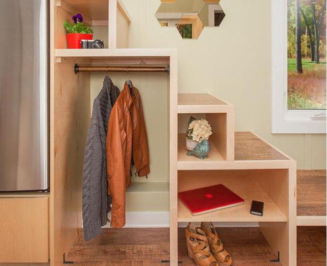 Trong ngôi nhà mọi góc nhỏ đều được tính toán vô cùng cẩn thận. Chiếc tủ lạnh được thiết kế vừa khiết đặt khéo léo trên kệ. Gầm cầu thang gỗ dẫn lên gác xép cũng được thiết kề với nhiều ngăn làm nơi lưu trữ đồ dùng cá nhân lý tưởng cho chủ nhà.