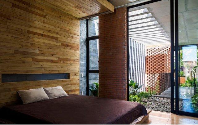Không gian nghỉ ngơi vô cùng thoáng đãng đặt cạnh một khu vườn nhỏ. Tường khu vực đầu giường còn được ốp gỗ sáng màu tạo không gian vừa thân thiện lại gần gũi với thiên nhiên.