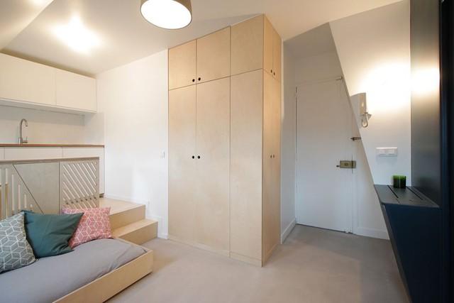 Chiếc tủ gỗ vuông vắn đựng quần áo và đồ dùng cá nhân được thiết kế cao cao sát trần vừa làm kho trữ đồ lý tưởng nhưng cũng khiến trần nhà có cảm giác như cao hơn.