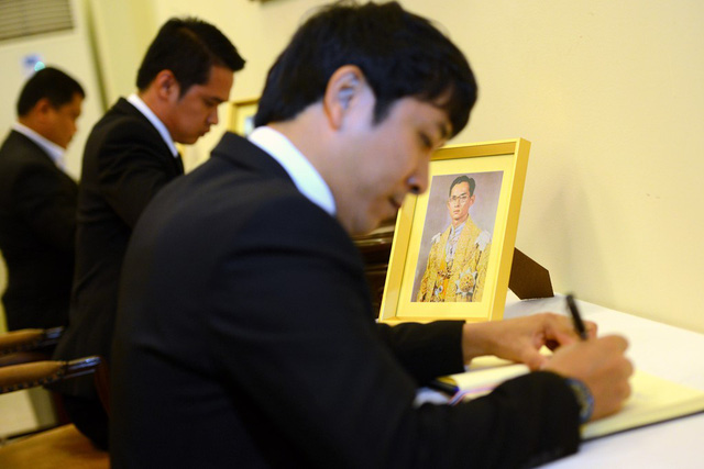 Mọi người lần lượt ghi sổ tang bên chân dung của đức vua.