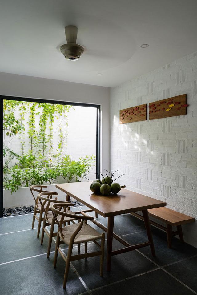 Phòng ăn với bộ bàn ghế gỗ rộng có view nhìn ra khu vườn xanh tươi.