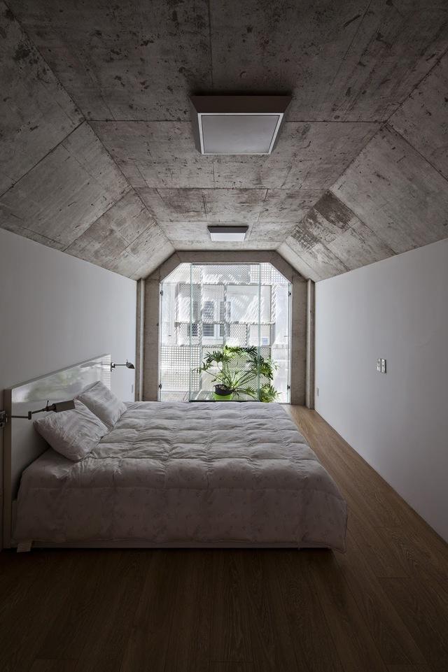 Phòng ngủ trên tầng 2 đơn giản nhưng tràn ngập ánh sáng với cây xanh và gió trời.