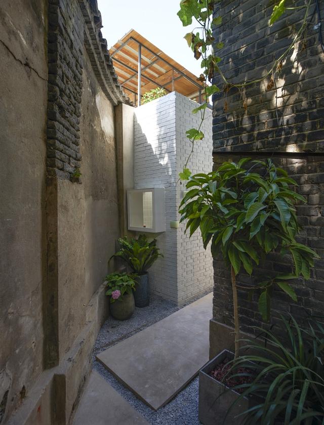 Ngôi nhà cấp 4 có lối vào láng xi măng quanh co nhỏ hẹp.