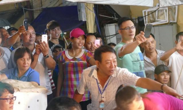 Nhiều người buôn bán, lái xe, bốc vác nhanh chân chạy đến chụp hình Thủ tướng làm kỷ niệm - Ảnh: LÊ KIÊN