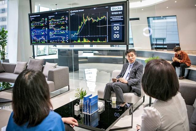 Khách hàng thảo luận các xu hướng giao dịch tại cửa hàng Seoul của Coinone, một công ty giao dịch tiền tệ ảo của Hàn Quốc.